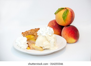 Home made peach cobbler with ice cream and whipped cream, on a white back ground with peaches.