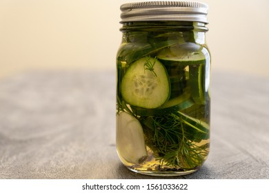 home made pickles in glass jar with dill weed,  garlic cloves/spices