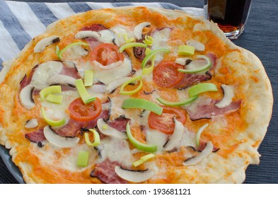Home made pizza with pork, tomato, salami and soda - Shutterstock ID 193681121