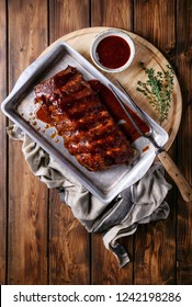 Home made pork ribs, glazed with barbecue sauce served with herbs and tomatoes, decorated with napkins over a rustic wooden background. Top View