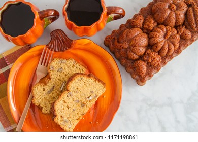 Home made pumpkin bread slices sitting on pumpkin plate with two cups of coffee and a whole loaf of bread made in decorative pan with space for text