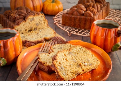 Home made pumpkin bread slices sitting on pumpkin plate with two cups of coffee and loaves of bread on wooden table