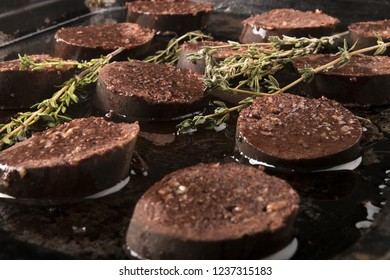 home made raw black pudding with oil and thyme in a pan