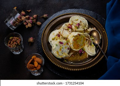 Home made ready to eat kulfi slices - saffron or kesariya flavoured with pistachio, cashew and almonds, selective focus, with rose petal, almonds, pista
