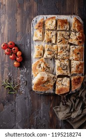 Home made rosemary focaccia flat bread served with baked tomatoes and fresh rosemary, with vintage napkin over a wooden background. Top View