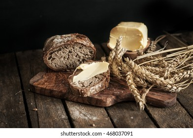 Home made rye bread with fresh butter on rustic wooden table. Ear of grain. Horizontal image