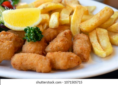 Home made scampi and chips served with mixed vegetables salad and lemon on top, English traditional menu, fresh food,selective focus