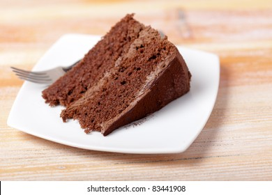 A home made slice of chocolate cake on a white plate with a fork.  Shallow depth of field with focus on the front of the cake.