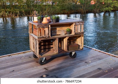 Home made storage furniture of wood boxes standing on a wooden jetty by a river