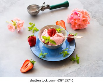 Home made strawberry ice cream in bowl with min leaves