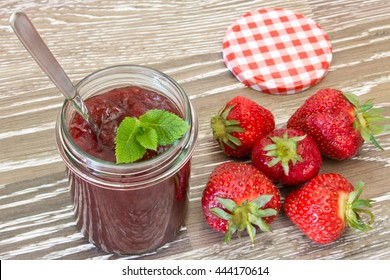 Home made strawberry jam in a jar with mint leaves