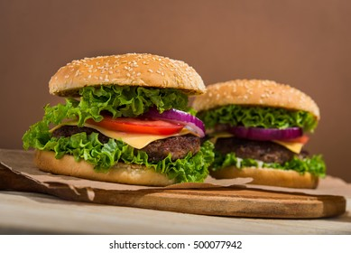 home made tasty burgers on wooden table