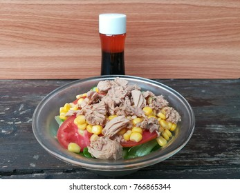 Home made tuna salad with spicy japanese dressing on old wooden table and wood background.