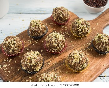 Home made vegan energy protein balls with oats, nuts, dates, dried fruit, flax and hemp seeds, chocolate nibs and maple syrup served in paper cases on wooden board.