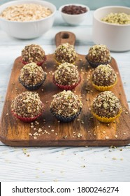 Home made vegan energy protein balls with oats, nuts, dates, dried fruit, flax and hemp seeds, chocolate nibs and maple syrup served in paper cases on wooden board. Vertical