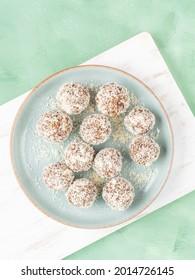 Balles de protéines d'énergie végétaliennes faites maison avec des paillettes de noix de coco, du beurre d'amande, de l'avoine, des noix, des dattes, des fruits secs, du lin et des graines de chanvre servies sur une planche en bois blanc.
