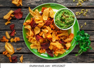Home made vegetable crisps from carrots, parsnips and beetroot with watercress guacamole