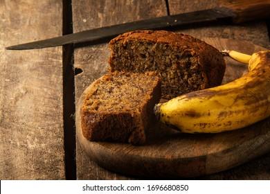 Hausgemacht sehr leckerer Kuchen mit Banane auf Holzhintergrund, Dorfstil. Rostik-Stil