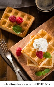 Home made waffles with raspberries and coffee on wooden background