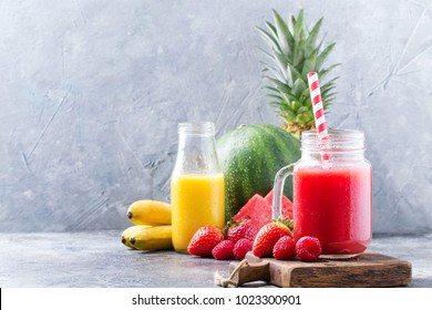 Home made watermelon and pineapple smoothie decorated with slices of watermelon, strawberries, bananas and whole pine apple over the pheasant blue stone background. Healthy drinks and food concept