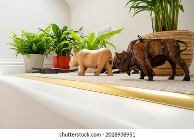 Home made wood carvings of wild animals seen on a carpeted ledge in a house. Also seen is a selection of lush houseplants.
