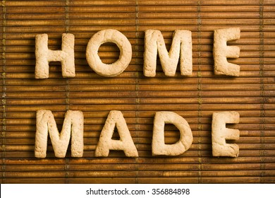 Home Made words composed of homemade biscuits letters arranged on wooden background.