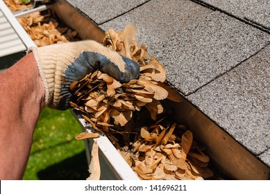 A home maintenance worker cleaning gutters