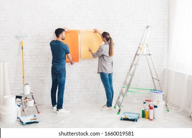 Home makeover and renovation. Young happy couple choosing in what color painting their new house interiors using paint examples