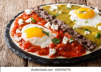 Home Mexican food: huevos divorciados with Frijoles refritos, two sauces roja and verde and cheese Queso Fresco on a corn tortilla macro. Horzontal