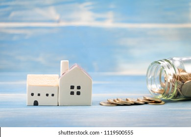 Home model and bottle bank with growing put on the vintage blue background, Saving money for buy house or loan to business investment for real estate concept.