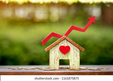Home model with heart and red arrow graph with growing value put on the coin in the public park, Business investment the real estate concept.