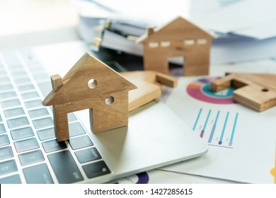 Home model for loan real estate to buy new for family or property mortgage investment concept: Wooden house models on laptop computer with chart report documents,wealth management for agency online.
