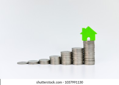 Home model on the growing coin stack for  in isolated white background concept of money saving for home buying fund