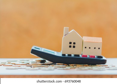 Home model put on the calculator and coin in the indoor, Loans for real estate or save money for buy a new house to family in the future concept.