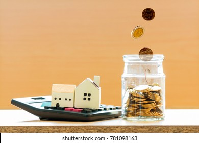 Home model put on the calculator and coin drop in the jar with growing money in the office, Business investment loan for real estate or save money for buy new house concept.