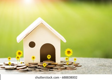 Home model put on the stacking golds coin with growing a collect interest put on the table on the sunlight in the public park, buying a new real estate or house to family in the future concept.