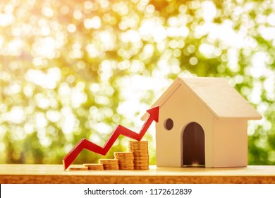 Home model and red arrow graph with growing value put on the stack gold coin on bokeh background in the public park, Business investment the real estate concept.