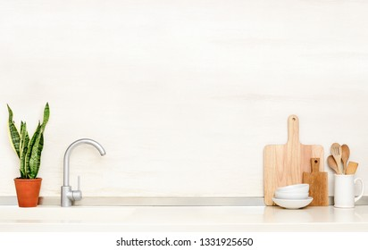 Home modern kitchen table top with sink and utensils standing on it, front view culinary background with blank space for a text