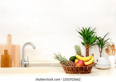 Home modern kitchen table top decorated with summer exotic fruits in a basket and home tropical plants ,front view culinary background with blank space for a text