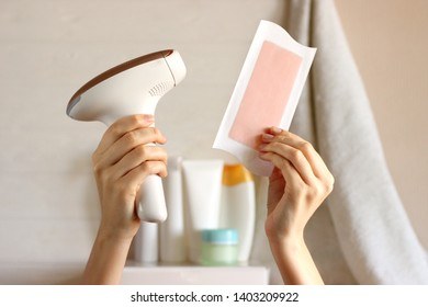 Home modern photoepilator and wax strip in female hands against the background of the bathroom. Untreated hair removal.