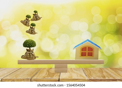 home and money bag with growing tree on top put on scales with balance,bokeh nature background,concept money saving,investments,financial planning in bank,for buying house and investing in real estate