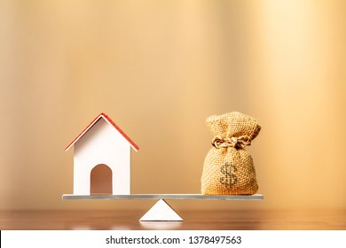 Home and money bag put on the scales with balance on brown background in the office, Saving for buy a new house or real estate and loan for plan business investment in the future concept.