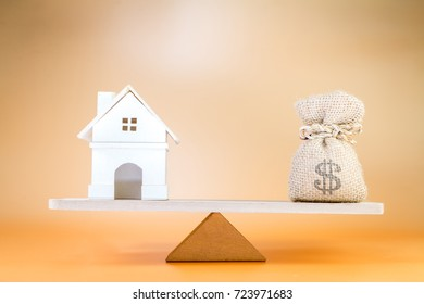 Home and money bag put on the scales with balance, Saving for buy a new house or real estate and loan for plan business investment in the future concept.