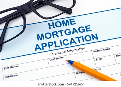 Home Mortgage Application with ballpoint pen and glasses.
