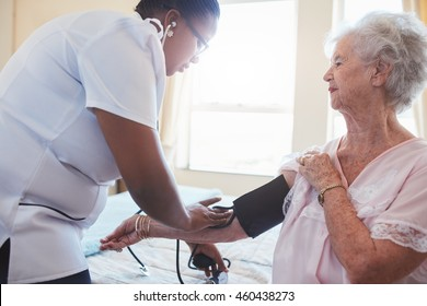 Home nurse doing blood pressure measurement of a senior patient. Doctor checking blood pressure of an elderly woman sitting on bed.
