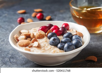 Home oatmeal with cranberries and blueberries. White plate, honey. Dark background. A delicious, healthy breakfast