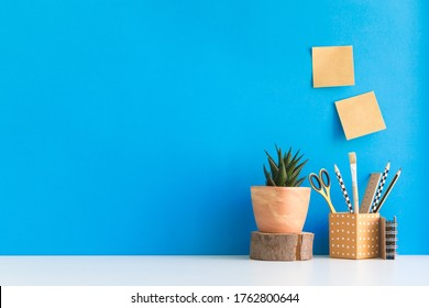 Home Office Hintergrund. Schreibtisch mit Noten, Vorräten, Design-Objekten, Pflanzen, Holzelementen und blauer Wand.
