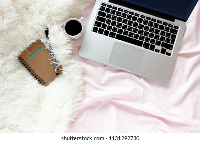 Home office in bed with laptop and mug of coffee, pen, kraft notepad on a pink linens and white fluffy blanket