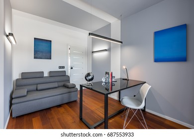 Home office with black table, white chair, gray couch and art