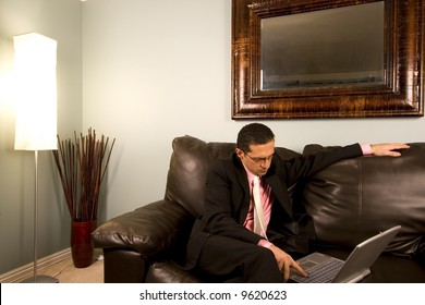 Home or Office - Businessman with his Glasses working on the Couch